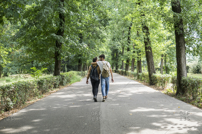 Back view of young gay couple with backpacks walking on a road