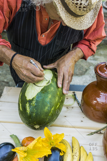 Senior man working on a watermelon with carving tool