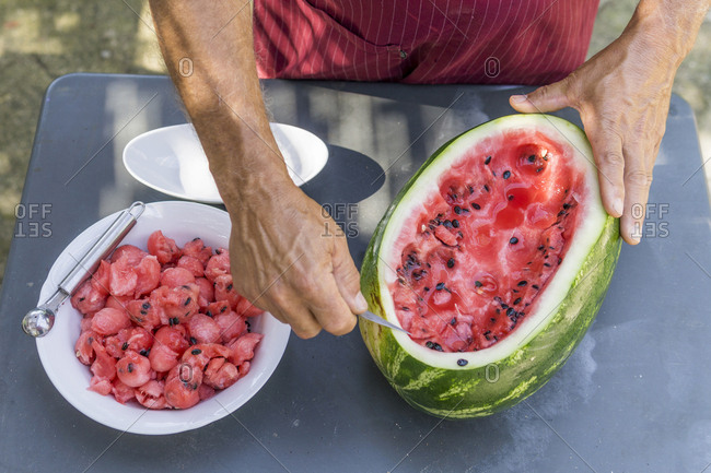 Close-up of man decorating a watermelon with carving tool