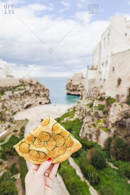Italy- Puglia- Polognano a Mare- woman's hand holding piece of zucchini focaccia