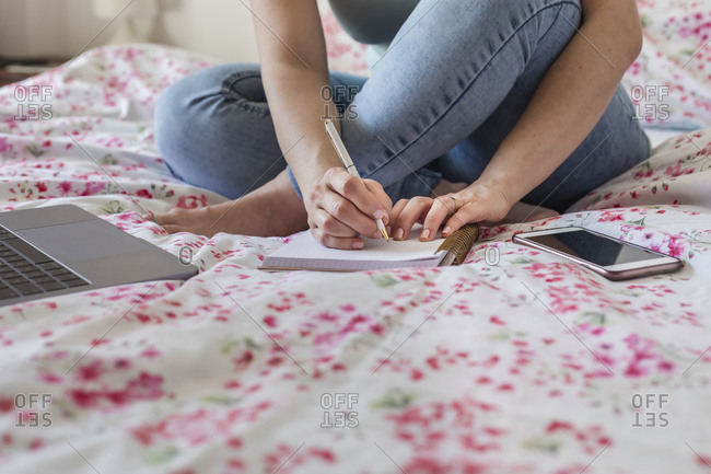 Woman sitting on bed at home working- partial view