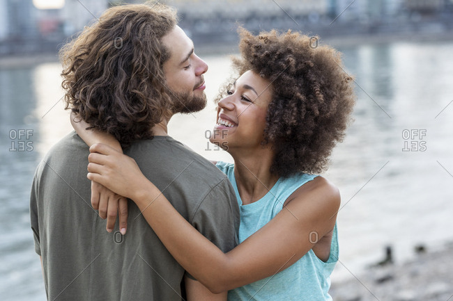 Happy young couple hugging at the riverside
