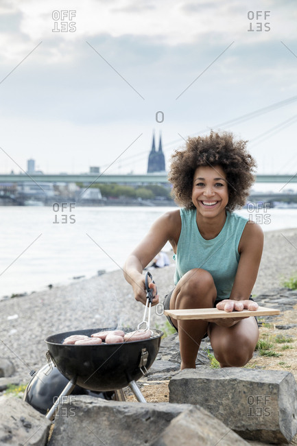 Germany- Cologne- portrait of smiling woman having a barbecue at the riverside