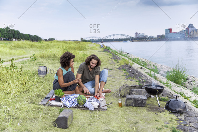 Germany- Cologne- couple having a barbecue at the riverside
