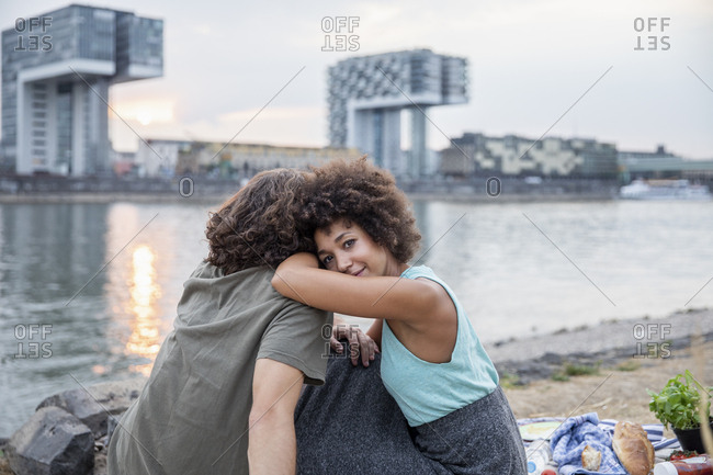 Germany- Cologne- couple relaxing at the riverside at sunset
