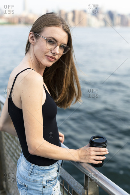 Young woman looking over East River- holding cup of coffee