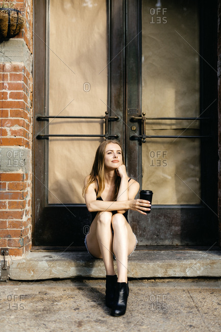 Young woman sitting in the street on a doorstep- holding a cup of coffee