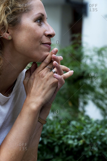 Profile of smiling woman with hand on chin