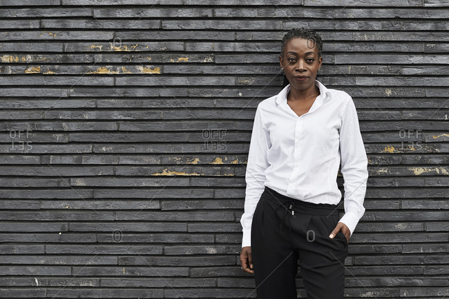 Portrait of smart businesswoman  wearing white shirt  and black trousers leaning against wall