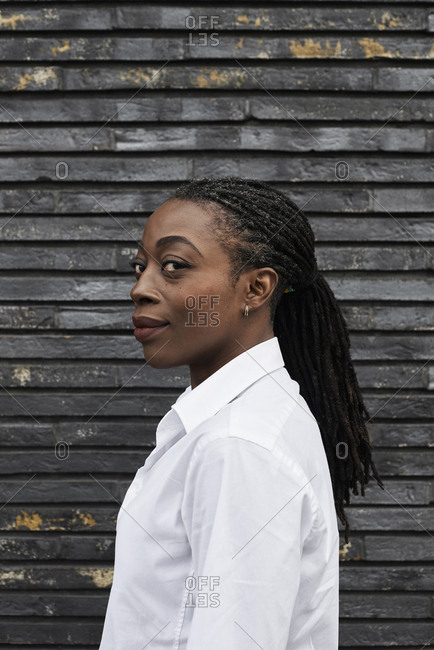 Portrait of smiling businesswoman with dreadlocks wearing white shirt