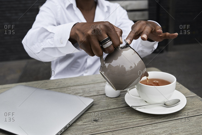Hands of businesswoman sitting on  terrace of a coffee shop pouring tea into a cup