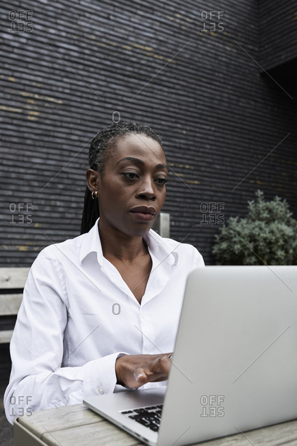 Portrait of businesswoman sitting on  terrace of a coffee shop working on laptop