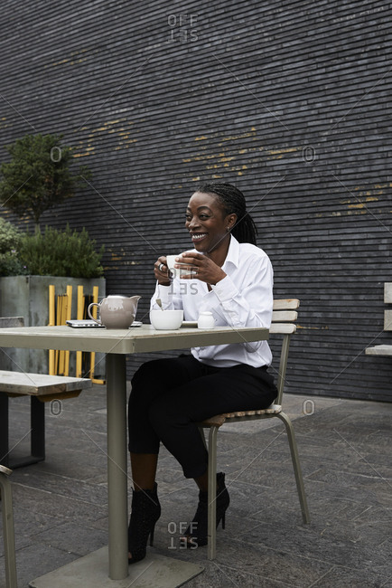 Laughing businesswoman sitting on  terrace of a coffee shop drinking tea