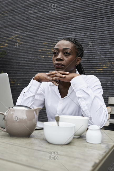 Portrait of pensive businesswoman sitting on terrace of a coffee shop