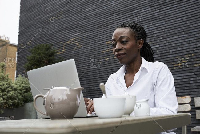 Portrait of smiling businesswoman sitting on terrace of a coffee shop working on laptop