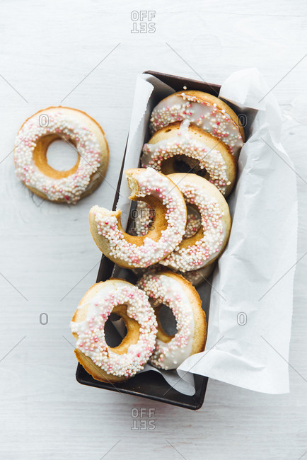 Cake pan of homemade doughnuts with icing and sugar beads