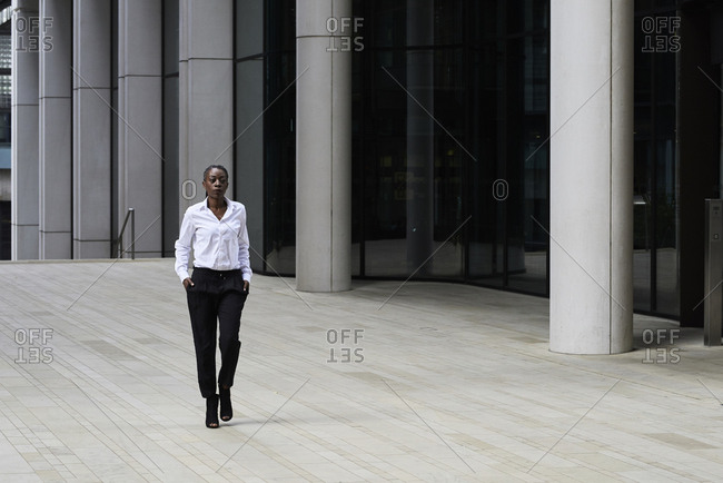 Businesswoman wearing white shirt and black trousers walking in front of a modern office building