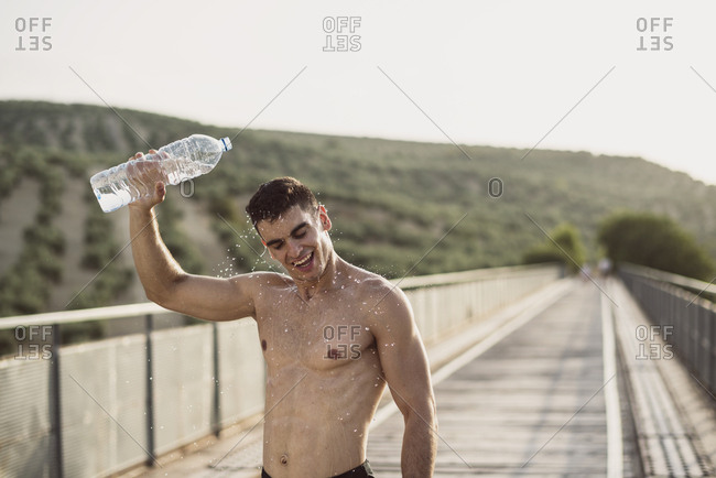 Young shirtless athlete on bridge pouring water above his head