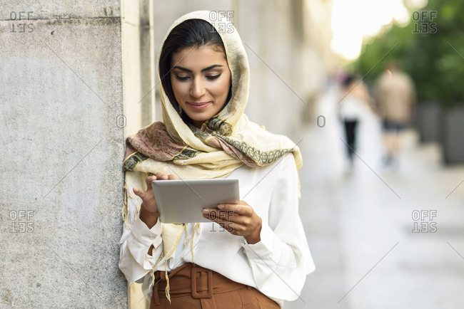 Spain- Granada- young muslim woman wearing hijab using tablet outdoor