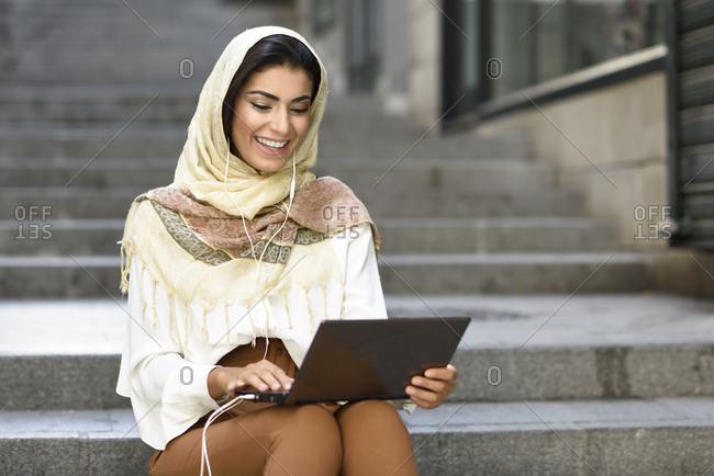 Spain- Granada- young muslim woman wearing hijab using laptop sitting on urban steps