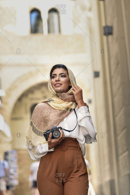 Spain- Granada- young Arab tourist woman wearing hijab- using camera during sightseeing in the city