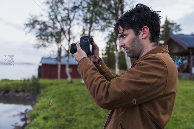 Sweden- Kiruna- Young man taking pictures of lake