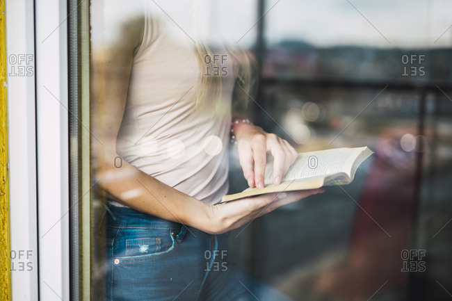 Close-up of young woman reading a book behind windowpane