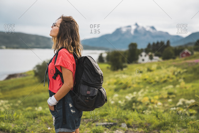Young woman with a backpack traveling Norwegian Lapland