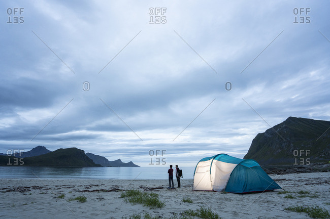 Norway- Lapland- Two people standing by tent on a beach at fjord