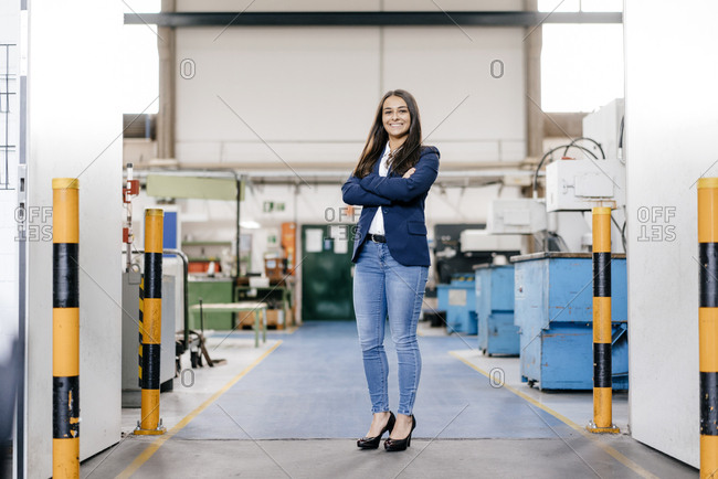 Confident woman working in high tech enterprise- standing in factory workshop with arms crossed
