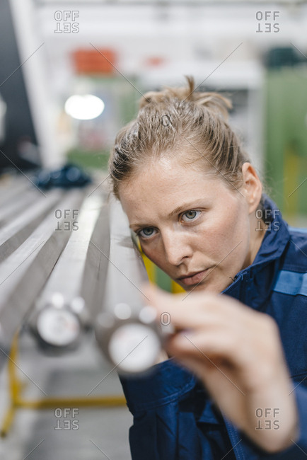 Young woman working as a skilled worker in a high tech company- checking steel rods
