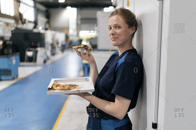 Woman working in high tech company- taking a break- eating pizza