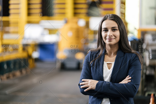 Confident woman standing in logistics center- with arms crossed