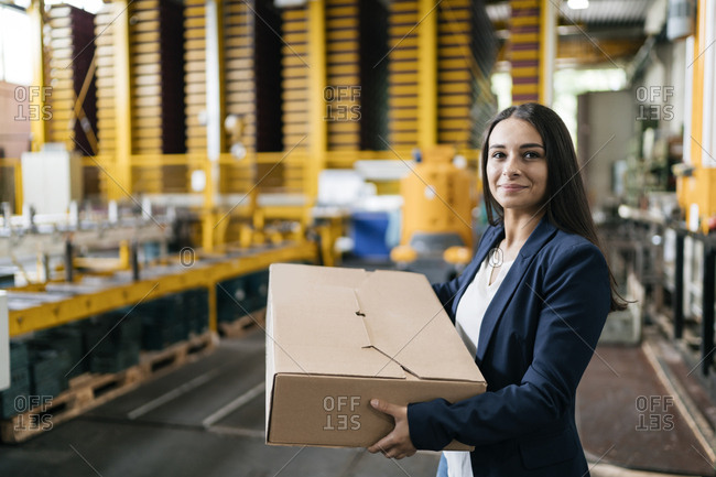Young woman working at parcel service- carrying parcel in warehouse