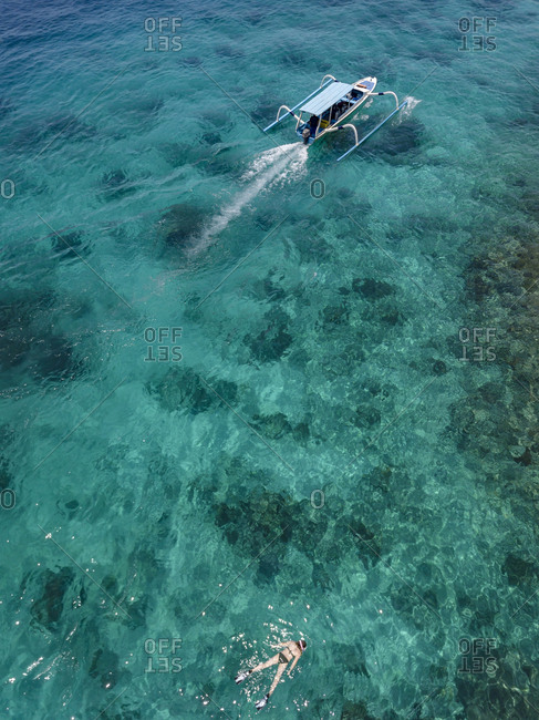 Indonesia- Bali- Aerial view of Blue Lagoon- snorkeler and banca boat