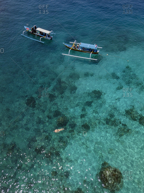 Indonesia- Bali- Aerial view of Blue Lagoon- snorkeler and banca boats