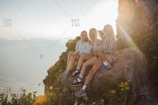 Switzerland- Grosser Mythen- three happy girlfriends on a hiking trip having a break at sunrise