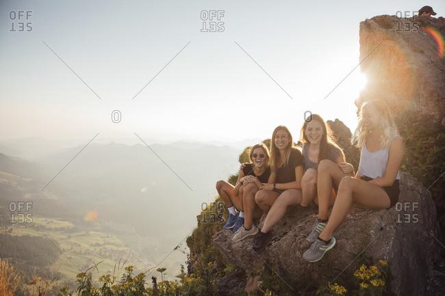 Switzerland- Grosser Mythen- four happy girlfriends on a hiking trip having a break at sunrise