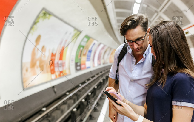 UK- London- young couple standing at underground station platform looking at cell phone