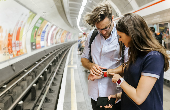 UK- London- couple waiting at   underground station platform looking at smartwatch