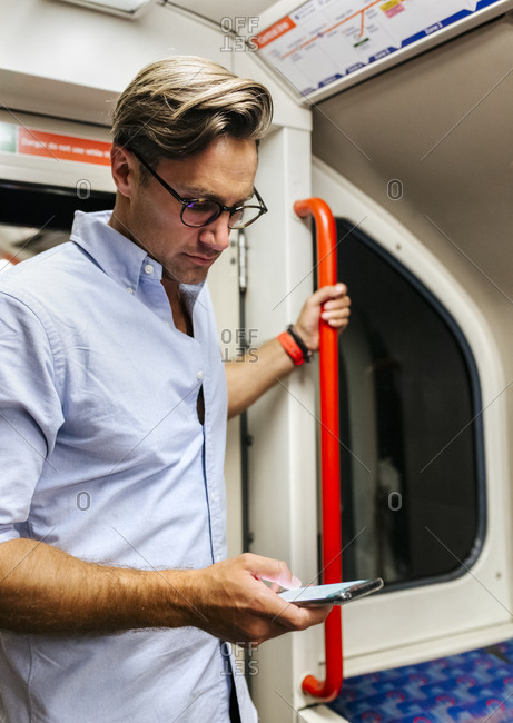 UK- London- businessman in underground train looking at cell phone