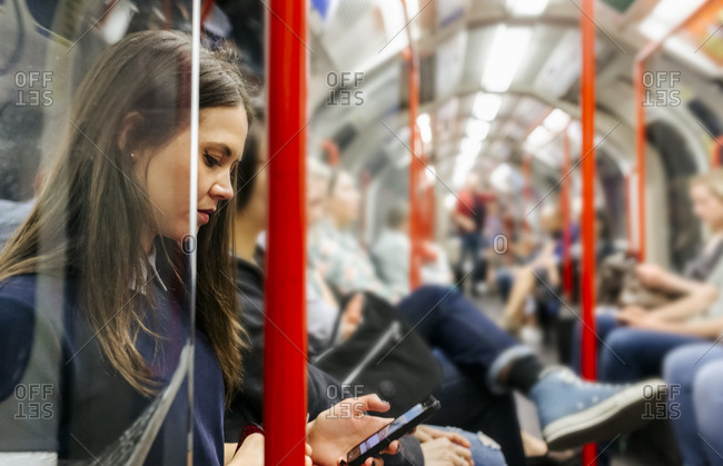 UK- London- young woman in underground train looking at cell phone