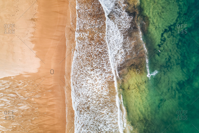 Spain- Asturias- Aerial view of surfers in the water on a beach