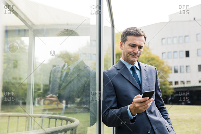 Serious businessman using cell phone leaning against glass front