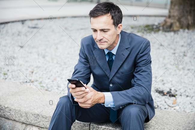 Businessman sitting down using cell phone in the city