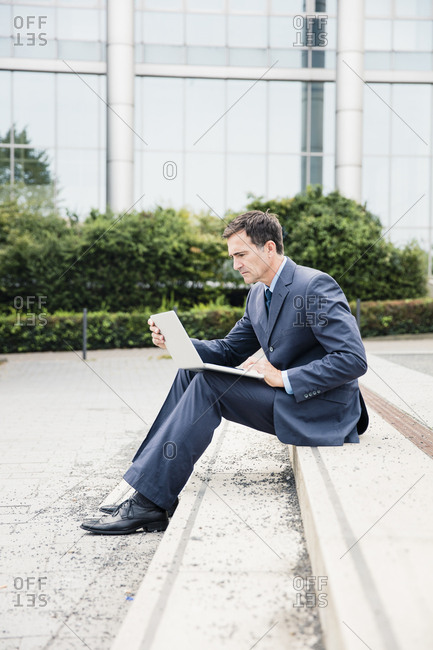 Serious businessman sitting down using laptop in the city