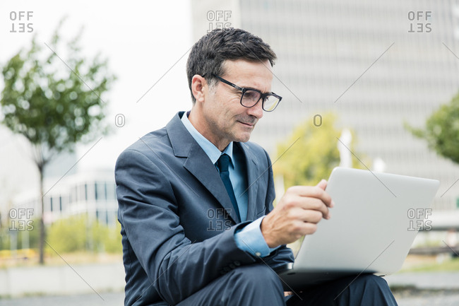 Businessman sitting down using laptop in the city