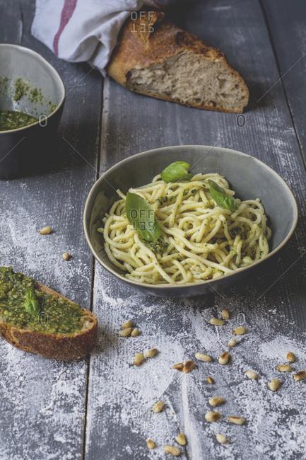 Homemade basil pesto- spaghetti in a bowl- rye baguette on wood