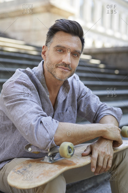 Portrait of relaxed mature man with skateboard sitting on stairs