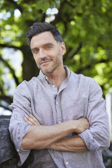 Portrait of smiling mature man with arms crossed leaning against wall